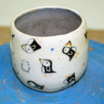 Wheel-thrown vessel hand-painted with underglazes and clear glazed